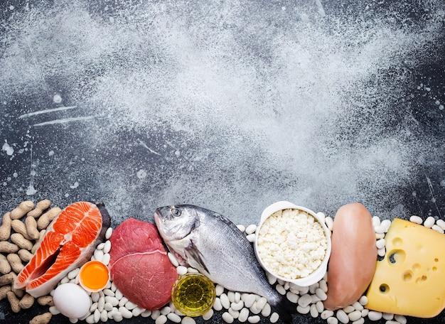 バランスの取れたケトン体生成低炭水化物ダイエットのための食品:魚、肉、オリーブオイル、鶏肉、卵、乳製品、豆、チーズ、ナッツ。灰色の背景。重量損失、上面図、テキスト用のスペースのためのケト製品のコンセプト
