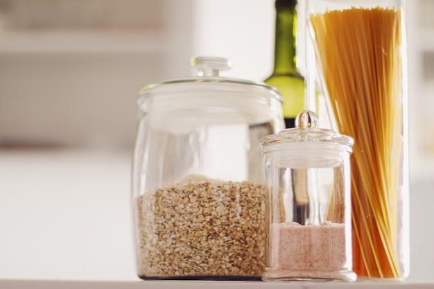 Пищевые продукты в стеклянных банках на кухне макароны крупы соль вино бакалея