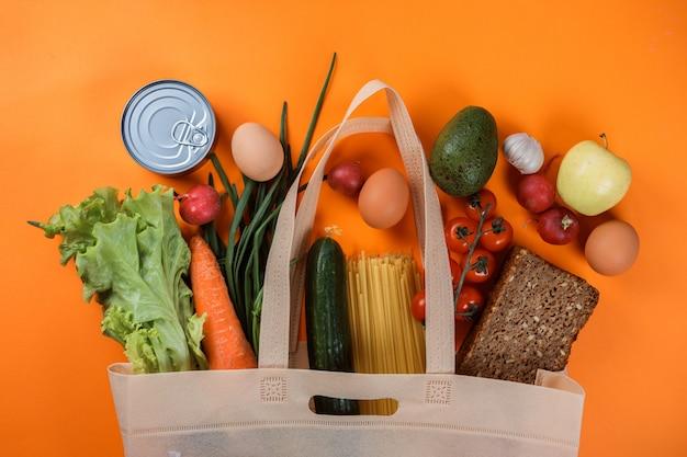 Пищевые продукты в хозяйственной сумке на апельсине.