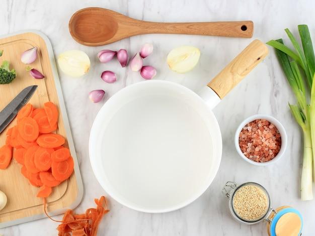 周りに野菜の材料が入った空の白いセラミック鍋。テキストまたは広告用の空白スペース。ブロッコリーとにんじんを使った野菜炒め物の調理の準備