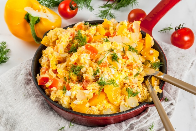 Food recipes, revoltillo de huevos, scrambled eggs a la dominicana, in portioned skillet, on white ,