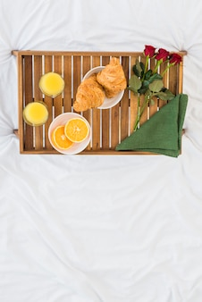 Food and roses on breakfast table on bed sheet