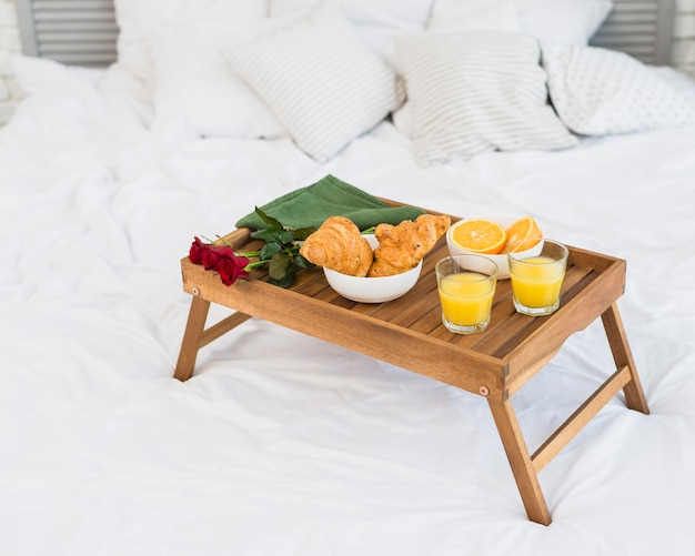 Food and roses on breakfast table on bed