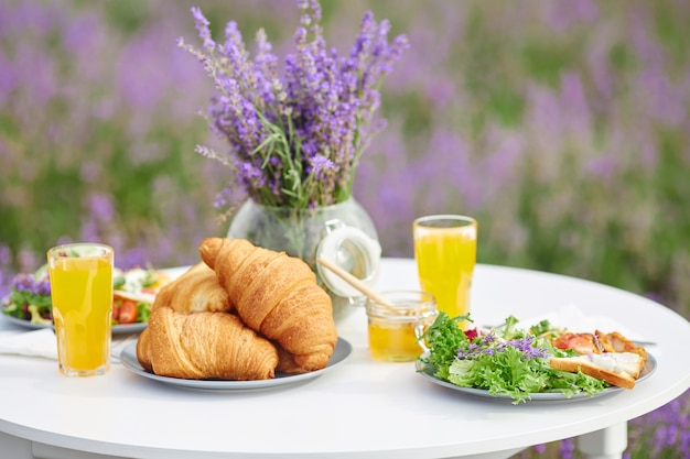 Food served for two on table in lavender field