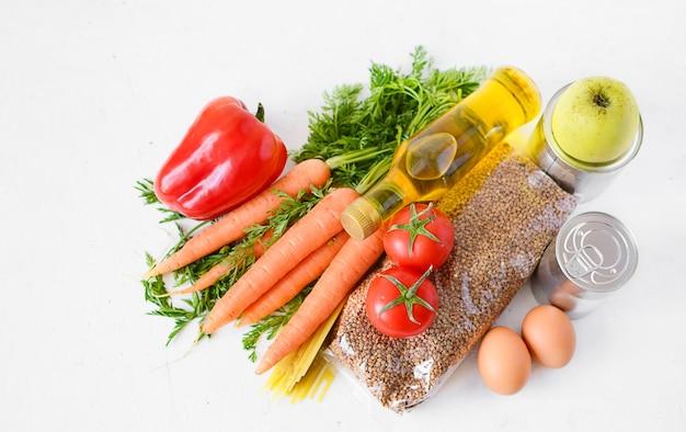 食品セット:白い表面にそば、パスタ、野菜、缶詰、卵、植物油。フードデリバリー、寄付。食料品は白い表面に在庫があります。上面図、コピースペース。