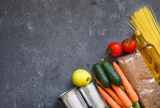 食品セット:暗い背景にそば、パスタ、野菜、缶詰、卵、植物油。フードデリバリー、寄付。白い背景の上の食料品の在庫。