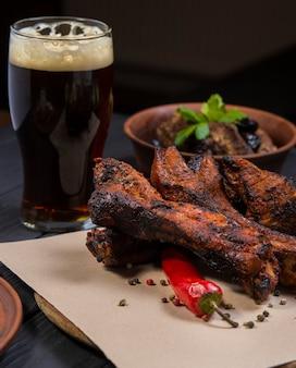Набор блюд с жареными свиными ребрышками стакан темного пива на черном деревянном фоне