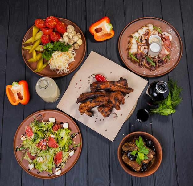 Набор блюд со свиными ребрышками на гриле, маринованными овощами, беконом, салатом цезарь и самогоном