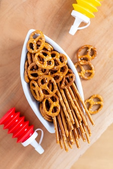Food snack salted crispy pretzel in ceramic boat on wood board with copy space