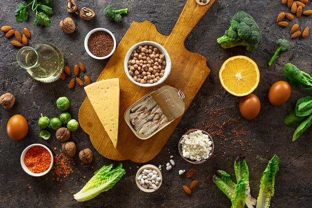Источники пищи омега-3 и здоровых жиров на темном фоне вид сверху. копировать пространство. овощи, морепродукты, орехи и семечки