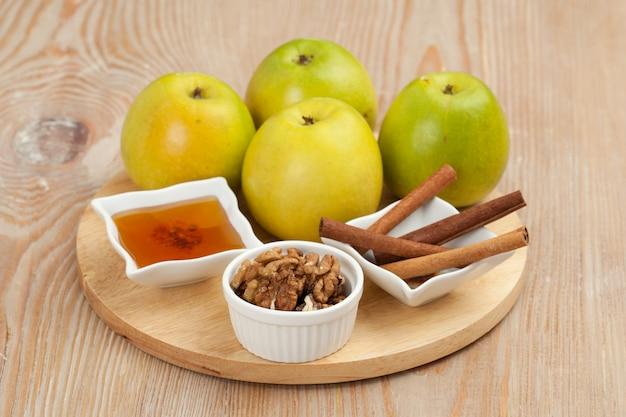 음식. 정물. 사과, 호두, 꿀, 계피 나무 보드