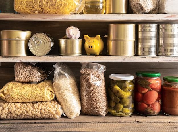食料品。バター、缶詰、シリアル、パスタが入った棚。予約します。寄付。