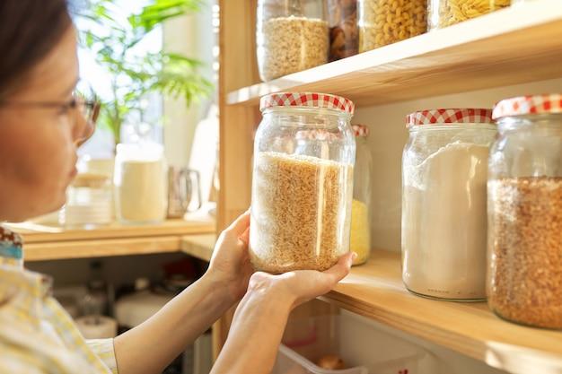 식료품 저장실에 식품 저장고, 쌀 항아리를 손에 들고 있는 여성. 식료품 저장실 내부, 식품 캔과 주방 용품이 있는 나무 선반
