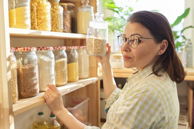 식품 저장, 저장 용기에 곡물 제품이있는 식료품 저장실의 나무 선반