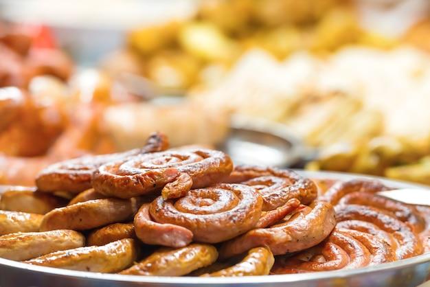 Уличная еда, праздничная традиционная азиатская кухня с овощами, мясом и колбасой на рынке