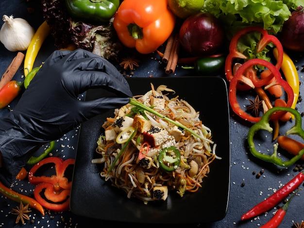 Фуд-стилист, украшающий азиатскую еду для презентации. концепция досуга хобби. женская рука в черных латексных перчатках