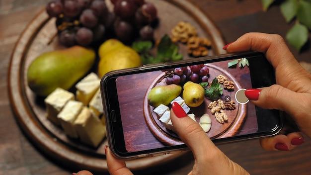 フードスタイリストやブロガーの女の子は、スマートフォンを使って料理ブログの写真を撮ります。才能のある食べ物