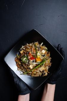 Фуд-стилист или блоггер, держащий восточную еду в черной тарелке на темном фоне. концепция досуга хобби. женщина рука в черных латексных перчатках. концепция свободного пространства