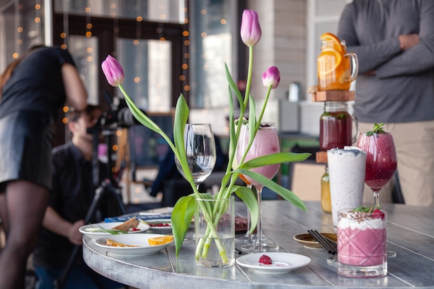 Food stylist and photographer decorate, preparing to shoot various cocktails, milkshakes, smoothies, flower tulips vase on table.