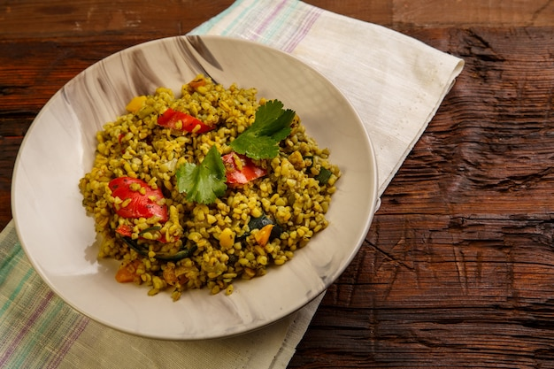 Food for suhoor in ramadan bulgur post with vegetables in a plate on a wooden table on a napkin. horizontal photo