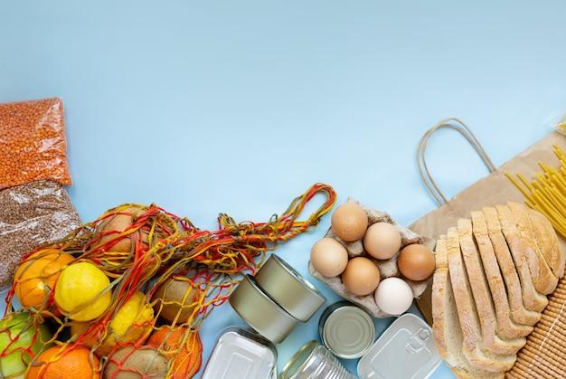 격리 격리 기간 동안 식량 공급 위기 식량 비축. 통조림 식품, 메밀, 파스타, 계란, 파란색 배경에 과일. 텍스트를 위한 공간을 복사합니다.