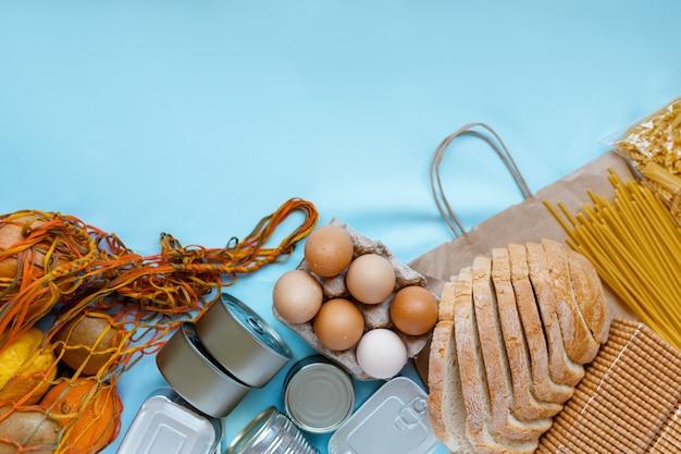 水色の背景に検疫隔離期間の食料供給危機食品在庫。パスタ、卵、果物、パン、缶詰食品。フードデリバリー、寄付、コロナウイルス検疫。コピースペース。