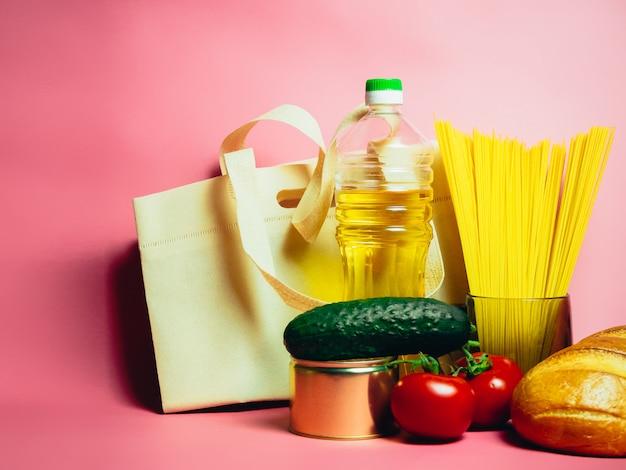 Продовольственные товары кризисного продовольственного запаса на карантинный период изоляции на розовом. вермишель, макароны, консервы, бананы, масло, хлеб.