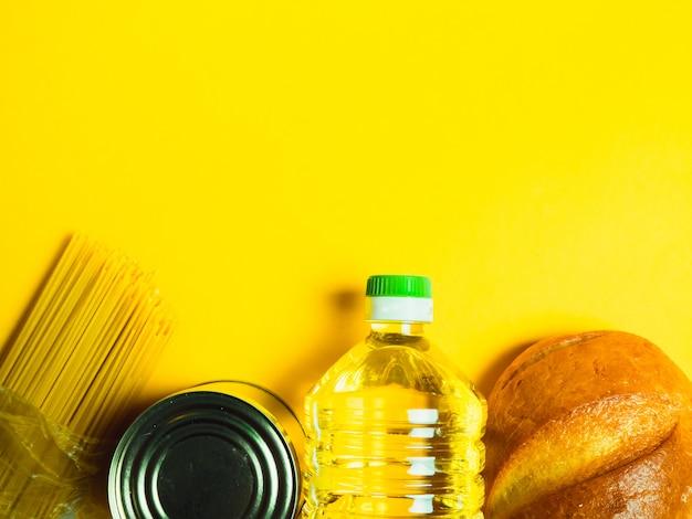 Продовольственные поставки кризис продовольственной изоляции запасов на желтой поверхности. вермишель, макароны, консервы, бананы, масло, хлеб.