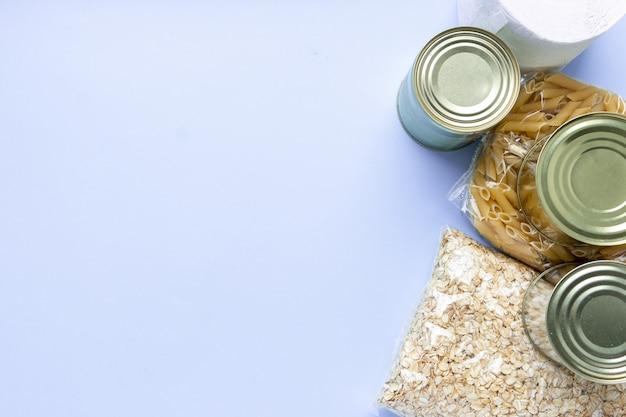 青色の背景に食料供給危機食品在庫分離期間。ご飯、パスタ、オートミール、缶詰、砂糖、トイレットペーパー。フードデリバリー、寄付、