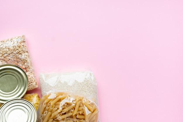 ピンクの背景に食料供給危機食料ストック分離期間。ご飯、パスタ、オートミール、缶詰、砂糖、トイレットペーパー。フードデリバリー、寄付、