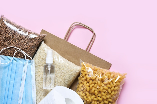 ピンクの背景に食料供給の危機。パスタ、そば、マスク、防腐剤、紙。寄付。平らに食べ物。