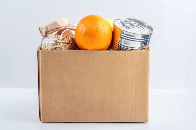 Food supplies during coronavirus quarantine and self-isolation. food delivery, donation, volunteer support. cardboard box with various canned food, pasta and cereal. eco packaging.