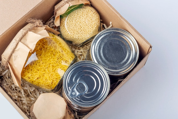 Food supplies during coronavirus quarantine and self-isolation. food delivery, donation, volunteer support. cardboard box with various canned food, pasta and cereal.