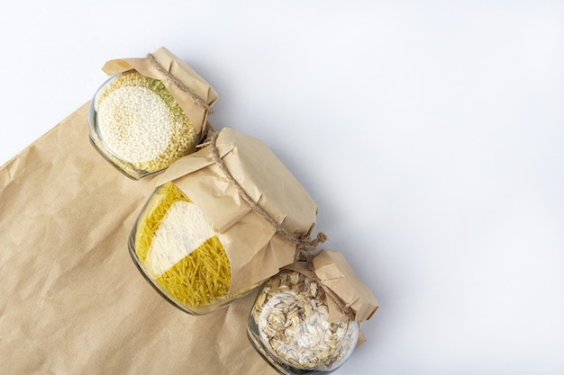 Food supplies during coronavirus quarantine and self-isolation. food delivery, donation, volunteer support. paper bag with cereal and pasta in glass jars.