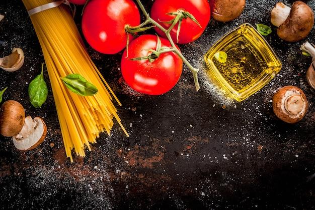 食品表面、夕食を調理するための材料。パスタスパゲッティ、野菜、ソース、スパイス、暗いさびた表面コピースペース平面図