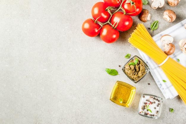 食品表面、夕食を調理するための材料。パスタスパゲッティ、野菜、ソース、スパイス、灰色の石の表面コピースペーストップビュー