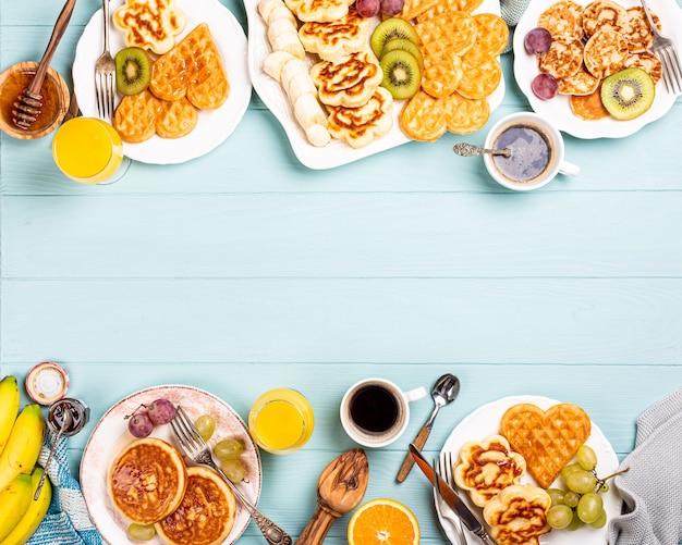 Поверхность еды со здоровым завтраком со свежими горячими вафлями, цветами, блинами, ягодным джемом и фруктами на бирюзовом столе, вид сверху, плоская планировка, копировальное пространство