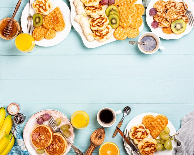 Food surface with healthy breakfast with fresh hot waffles hearts, pancakes flowers with berry jam and fruits on turquoise table, top view, flat lay, copy space