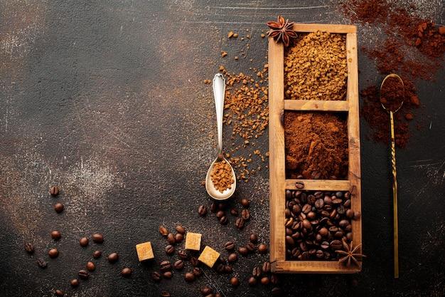 Пищевая поверхность с тремя видами кофе: зерновой, молотый, растворимый в деревянном ящике на старой бетонной коричневой поверхности. деревенский стиль. выборочный фокус. вид сверху.