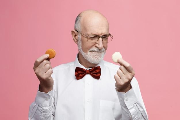 食品、お菓子、お菓子のコンセプト。 2つのカラフルなマカロンクッキーを持って、眉をひそめ、それらの間で選択し、眼鏡と蝶ネクタイを身に着けている甘い歯を持っている優柔不断なシニアひげを生やした男性