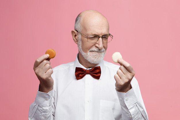 Food, sweets and treats concept.  indecisive senior bearded male having sweet tooth holding two colorful macarons cookies, frowning, choosing between them, wearing eyeglasses and bow tie