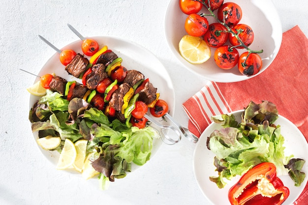 Food table with beef grilled meat kebab with vegetables and sauce top view