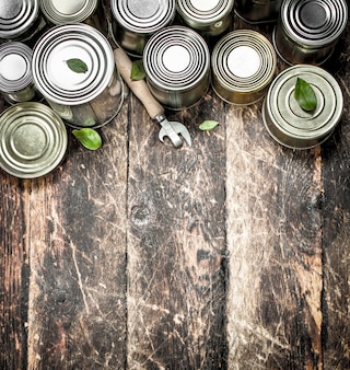 Food in tin cans with opener. on a wooden background.