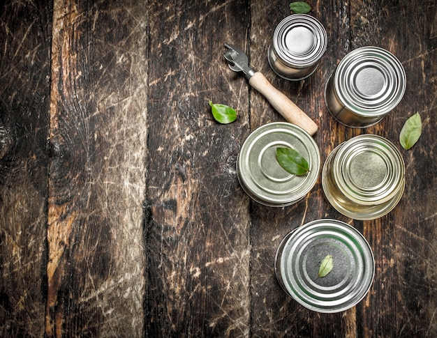 Food in tin cans with opener on wooden table.