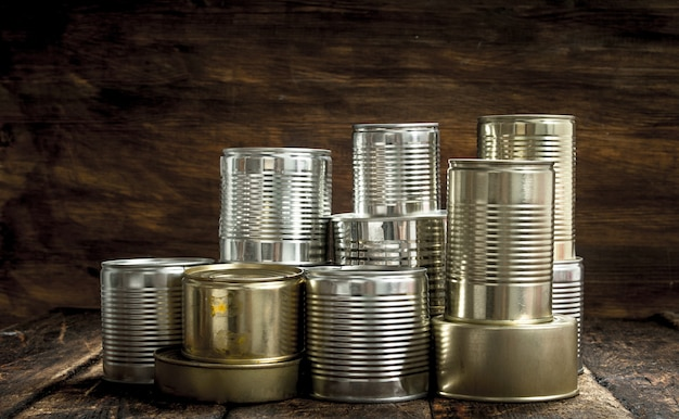 Food in tin cans on a wooden background