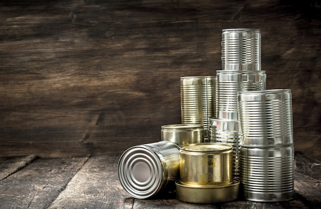 Food in tin cans on wooden table.