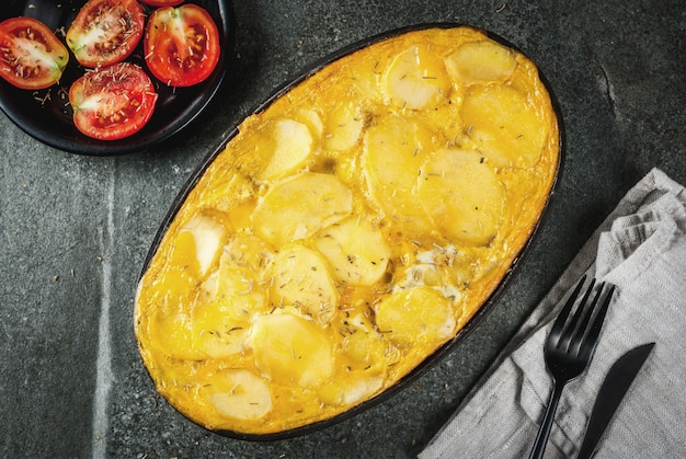Food. traditional dish tortilla de patatas  a casserole from potatoes and eggs, on a black stone table.