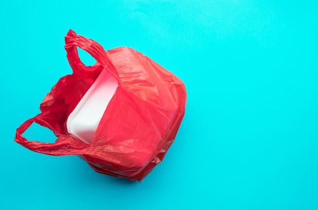 Упаковка мусора в красный полиэтиленовый пакет