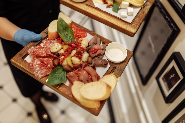 Food tray with delicious salami, pieces of sliced ham, sausage, olives - meat platter with selection.