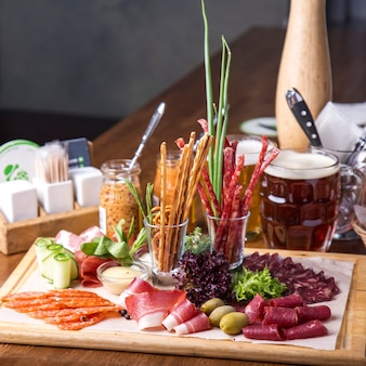 Food tray with delicious salami, pieces of sliced ham and  sausages. cutting sausage and cured meat on a celebratory table.